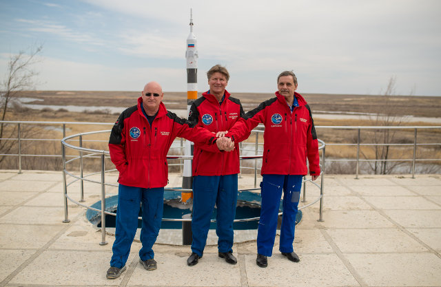 Astronaut Scott Kelly with cosmonauts Gennady Padalka and Mikhail Kornienko in front of a model of the Soyuz rocked used for the launch (Photo NASA/Bill Ingalls)