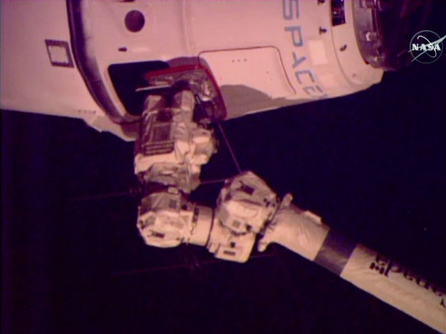 The SpaceX Dragon spacecraft captured by the International Space Station's robotic arm during its CRS-6 mission (Image NASA TV)