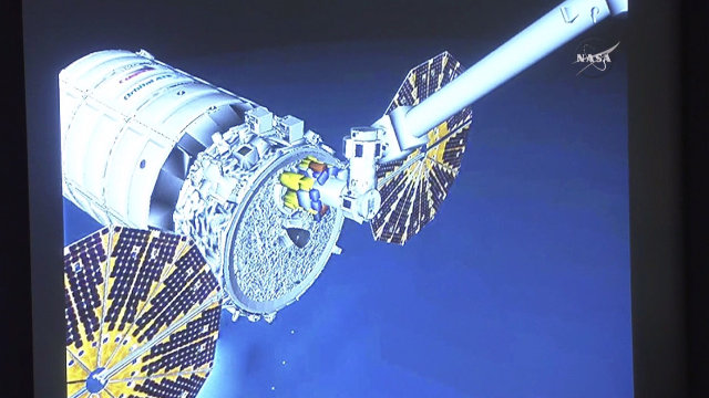 Rendering showing the Cygnus spacecraft captured by the Canadarm2 robotic arm from the International Space Station (Image NASA TV)