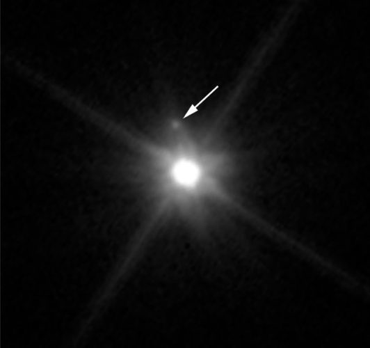 The dwarf planet Makemake seen by the Hubble Space Telescope with its moon indicated by the arrow (Image NASA, ESA, and A. Parker and M. Buie (SwRI))