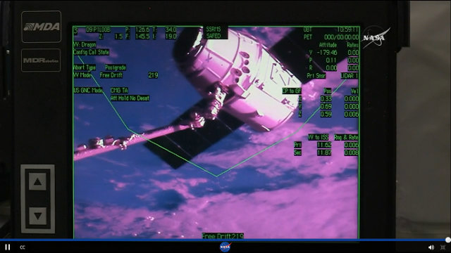 SpaceX Dragon space cargo ship captured by the International Space Station's robotic arm in its CRS-9 mission (Image NASA TV)