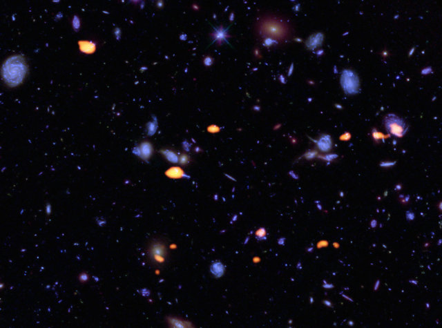Galaxies rich in carbon monoxide seen in orange together with the ones seen by Hubble in blue (Image B. Saxton (NRAO/AUI/NSF); ALMA (ESO/NAOJ/NRAO); NASA/ESA Hubble)