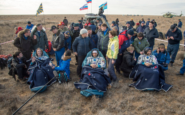 Kate Rubins, Anatoly Ivanishin and Takuya Onishi surrounded by support personnel after landing (Photo NASA/Bill Ingalls)