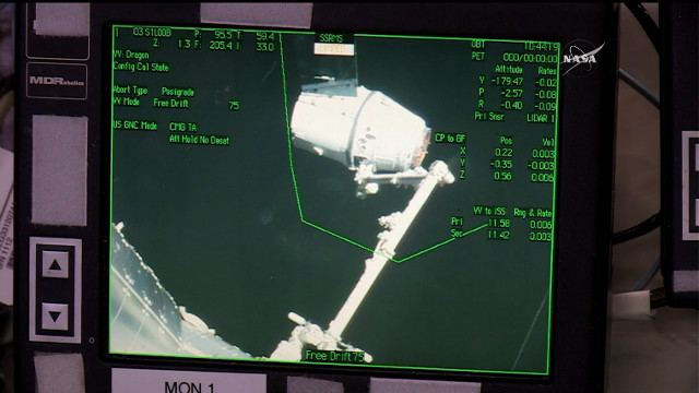 The Dragon space cargo ship captured by the International Space Station's robotic arm (Image NASA TV)