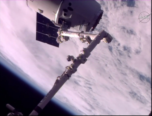 The Dragon cargo spacecraft captured by the Canadarm2 robotic arm (Image NASA TV)