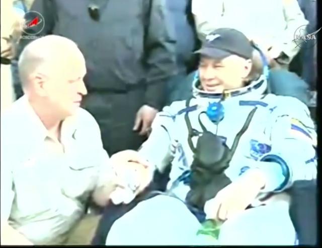 Oleg Novitskiy assisted after his landing (Image NASA TV)