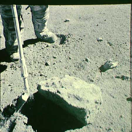 The sampe 66095 aka Rusty Rock getting collected (Photo NASA)