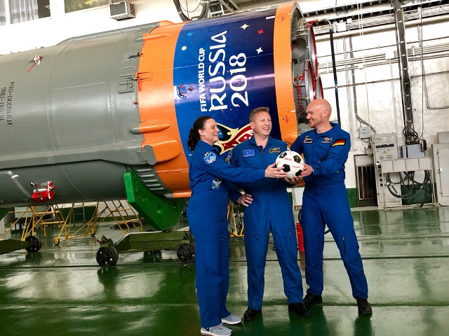 Serena Auñón-Chancellor, Sergey Prokopyev and Alexander Gerst in front of the Soyuz-FG rocket with the 2018 FIFA World Cup emblem (Photo courtesy Roscosmos)