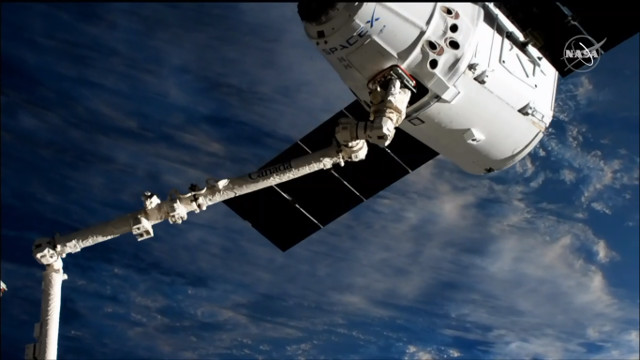 The Dragon cargo spacecraft captured by the Canadarm2 robotic arm in its CRS-18 mission (Image NASA TV)